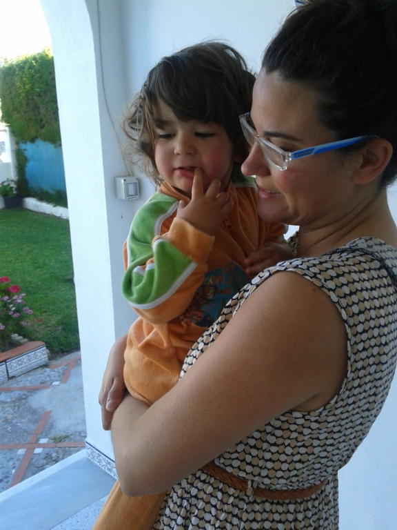 Mujer carga en brazos a su hijo