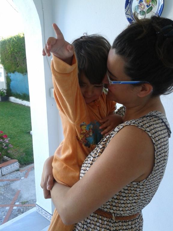 Mujer con gafas carga en brazos a su hijo