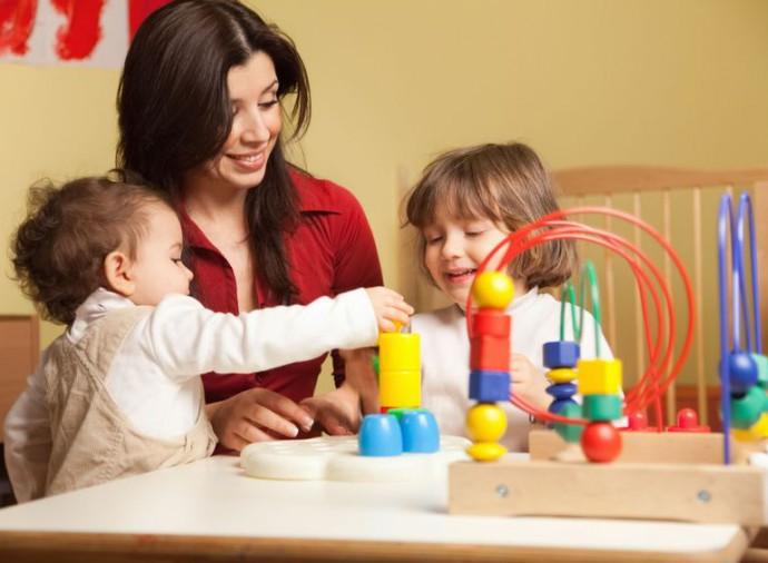 Madre juega con sus hijos con varios juguetes