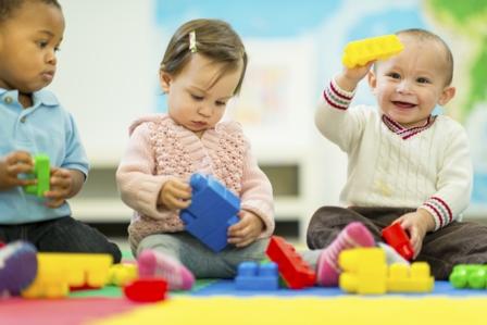 Niños jugando y sonriendo en el suelo