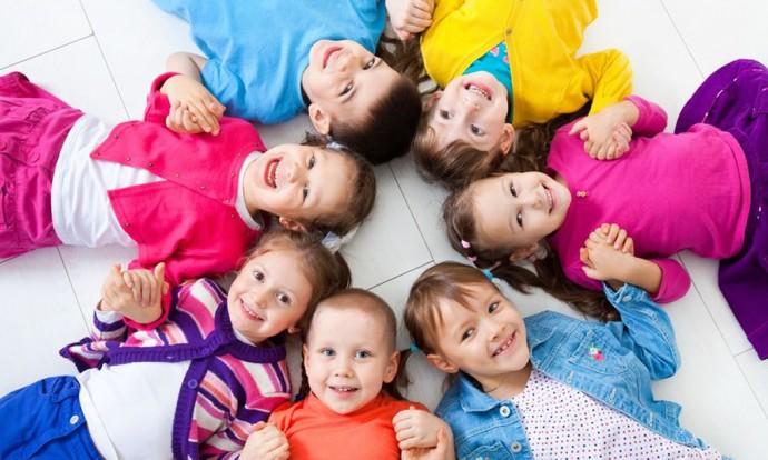 Niños tumbados en círculo sonríen